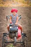 Szczęśliwy dziecko w czerwonych bandanach i lampasa trójniku siedzi na tiller na polu dziewczynka kierowcy kultywator Zdjęcia Stock