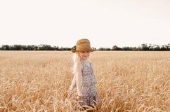 Szczęśliwy dziecko w jesieni pszenicznym polu Piękna dziewczyna z białym włosy w słomianym kapeluszu z dojrzałą banatką w rękach Zdjęcia Stock