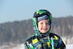 Szczęśliwy dziecko w kolor kurtce przeciw śniegowi i niebu Fotografia Royalty Free