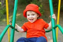 Szczęśliwy dziecko w pomarańczowym kapeluszu na huśtawce Obrazy Royalty Free