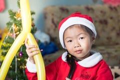 Szczęśliwy dziecko w Santa kapeluszu z prezentem blisko choinki, Ch Obrazy Royalty Free
