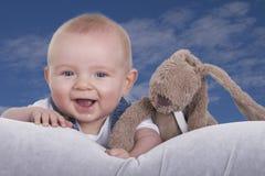 Szczęśliwy dziecko z faszerującym zwierzęciem przeciw niebieskiemu niebu Fotografia Stock