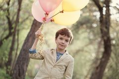Szczęśliwy dziecko z kolorowymi balonami w świętowaniu Zdjęcia Stock