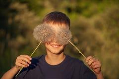 Szczęśliwy dziecko z puszystym dandelion ono przygląda się w letnim dniu Chłopiec jest uśmiechnięta, styl życia zdjęcie stock