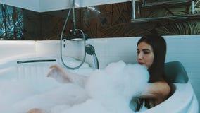 Szczęśliwy dziewczyna wp8lywy skąpanie piana w łazience pełno wanna Ciosu mydła piana _ zbiory