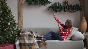 Szczęśliwy dziewczyny dopatrywanie leje się zawartość na linii w mądrze telefonu obsiadaniu na kanapie w zimie w domu zbiory wideo