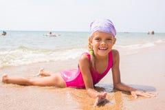 Szczęśliwy dziewczyny lying on the beach na piasku blisko wody na plaży i uśmiechać się szczęśliwie spojrzenia w ramę Obraz Royalty Free