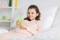 Szczęśliwy dziewczyny lying on the beach w łóżku z smartphone w domu Obraz Royalty Free