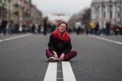 Szczęśliwy dziewczyny obsiadanie na drodze po środku ulicy obrazy stock