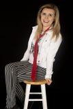 Szczęśliwy dziewczyny obsiadanie na stolec oparty z powrotem ono uśmiecha się Obraz Stock