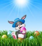 Szczęśliwy Easter królik jest ubranym kapelusz niesie Easter jajka w trawie ilustracji