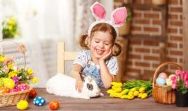 Szczęśliwy Easter! szczęśliwa śmieszna dziecko dziewczyna bawić się z królikiem Fotografia Royalty Free