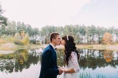 Szczęśliwy elegancki fornal i jego powabna nowa żona buziaka na brzeg lasowy jezioro obrazy royalty free