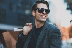 Szczęśliwy elegancki młodego człowieka odprowadzenie w miastowej ulicie i cieszyć się Black Friday zakupy w modnym przechujemy w  obraz royalty free