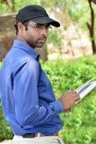 Szczęśliwy elegancki młodego człowieka writing & czytania książkowy plenerowy obrazy stock