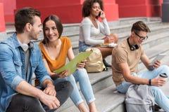 Szczęśliwy facet i dziewczyna opowiada podczas gdy siedzący na uniwersyteckich krokach zdjęcia royalty free