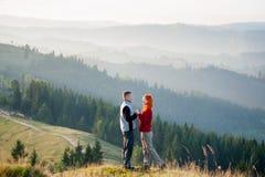 Szczęśliwy facet i dziewczyna w górach w ranku Fotografia Stock