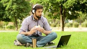 Szczęśliwy facet jest siedzący na trawie w oark i patrzeć laptop Jest słuchający muzyczny i uśmiechnięty Facet gryźć kawałek zbiory wideo