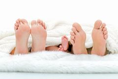 Szczęśliwy familiy w łóżku Macierzyści ojca i dziecka cieki pod koc Drzewne pary nogi Obrazy Royalty Free