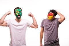 Szczęśliwy fan piłki nożnej Brazylia świętuje wygranę nad wzburzonym fan piłki nożnej Niemcy drużyna narodowa. z malującą twarzą  obrazy royalty free