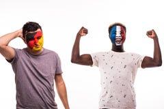 Szczęśliwy fan piłki nożnej Francja świętuje wygranę nad wzburzonym fan piłki nożnej Niemcy drużyna narodowa. z malującą twarzą o obrazy royalty free