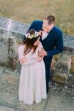 Szczęśliwy fornal trzyma jego ładnej panny młodej podczas gdy oba stoją na antyka kamienia schodkach Wysokiego kąta widok Zdjęcie Stock