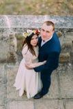 Szczęśliwy fornala obejmowanie z jego ładną panną młodą podczas gdy oba stoją na antyka kamienia schodkach Wysokiego kąta widok Zdjęcie Royalty Free
