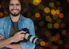 szczęśliwy fotograf z kamerą na rękach Pomarańcze i zieleni bokeh nasunięcie i tło zdjęcie stock
