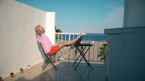 Szczęśliwy freelancer kończy jego pracy na laptopie podczas gdy siedzący na seaview tarasie fotografia royalty free