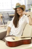 Szczęśliwy gitara gracza obsiadanie na kanapie Obraz Stock