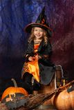 Szczęśliwy Halloween! Rozochocona mała dziewczynka w czarownica kostiumu obsiadaniu Zdjęcia Royalty Free