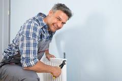 Szczęśliwy hydraulika naprawiania grzejnik obrazy stock