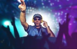 Szczęśliwy i chłodno DJ bawić się muzykę przy partyjnym wydarzeniem w noc klubie miesza techno piosenki na światła tle ro zdjęcia royalty free