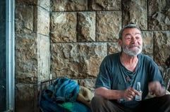 Szczęśliwy i uśmiechnięty biedny bezdomny mężczyzna obsiadanie w cieniu budynku na miastowej ulicie w mieście obraz stock