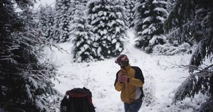 Szczęśliwy i z podnieceniem turystyczny mężczyzna po środku śnieżny lasowy pełnego zakrywającego śnieg zatrzymywał podziwiać wszy zbiory wideo