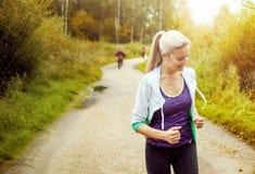 Szczęśliwy i zdrowy dziewczyna biegacz na drodze z innymi biegaczami w odległości Fotografia Royalty Free