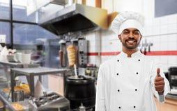Szczęśliwy indyjski szef kuchni pokazuje aprobaty przy kebabu sklepem zdjęcia stock
