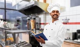 Szczęśliwy indyjski szef kuchni z książką kucharską przy kebabu sklepem zdjęcia stock