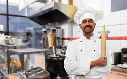 Szczęśliwy indyjski szef kuchni z wałkownicą przy kebabu sklepem obraz royalty free