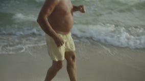 Szczęśliwy Kaukaski Amerykański męski senior cieszy się jego plenerowego styl życia tana na plażowym usa 4k zdjęcie wideo