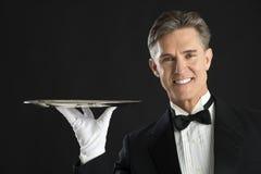 Szczęśliwy kelner W smokingu przewożeniu Słuzyć tacę zdjęcia stock