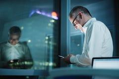 Szczęśliwy kierownik Używa Smartphone W Ciemnym biurze Przy nocą obrazy royalty free