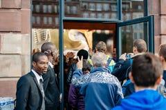 Szczęśliwy klient wchodzić do Apple Store z zwycięstwo znakiem Zdjęcia Stock