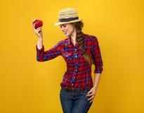 Szczęśliwy kobieta hodowca odizolowywający na kolorze żółtym pozuje z jabłkiem Fotografia Royalty Free