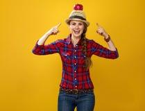 Szczęśliwy kobieta hodowca odizolowywający na kolorze żółtym wskazuje na jabłku na głowie Zdjęcia Royalty Free