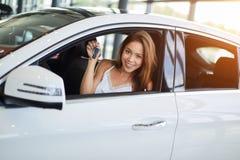 Szczęśliwy kobieta kierowca w białym samochodzie trzyma samochodowych klucze w jej nowym samochodzie przy samochodowego przedstaw zdjęcie royalty free