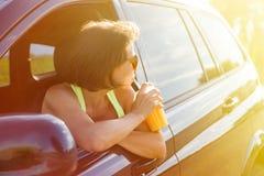 Szczęśliwy kobieta kierowca zatrzymuje relaksować, cieszy się podróż, napój lub obrazy stock