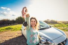 Szczęśliwy kobieta kierowcy chwyta samochód wpisuje blisko jej nowego samochodu Obraz Stock