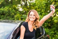 Szczęśliwy kobieta kierowcy chwyta samochód wpisuje w jej nowym samochodzie Zdjęcia Stock