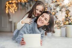 Szczęśliwy kobieta model z krótkim ciemnym włosy i jej adorabe mała dziewczyna zabawę wpólnie, świętujemy boże narodzenia, wymien obraz stock